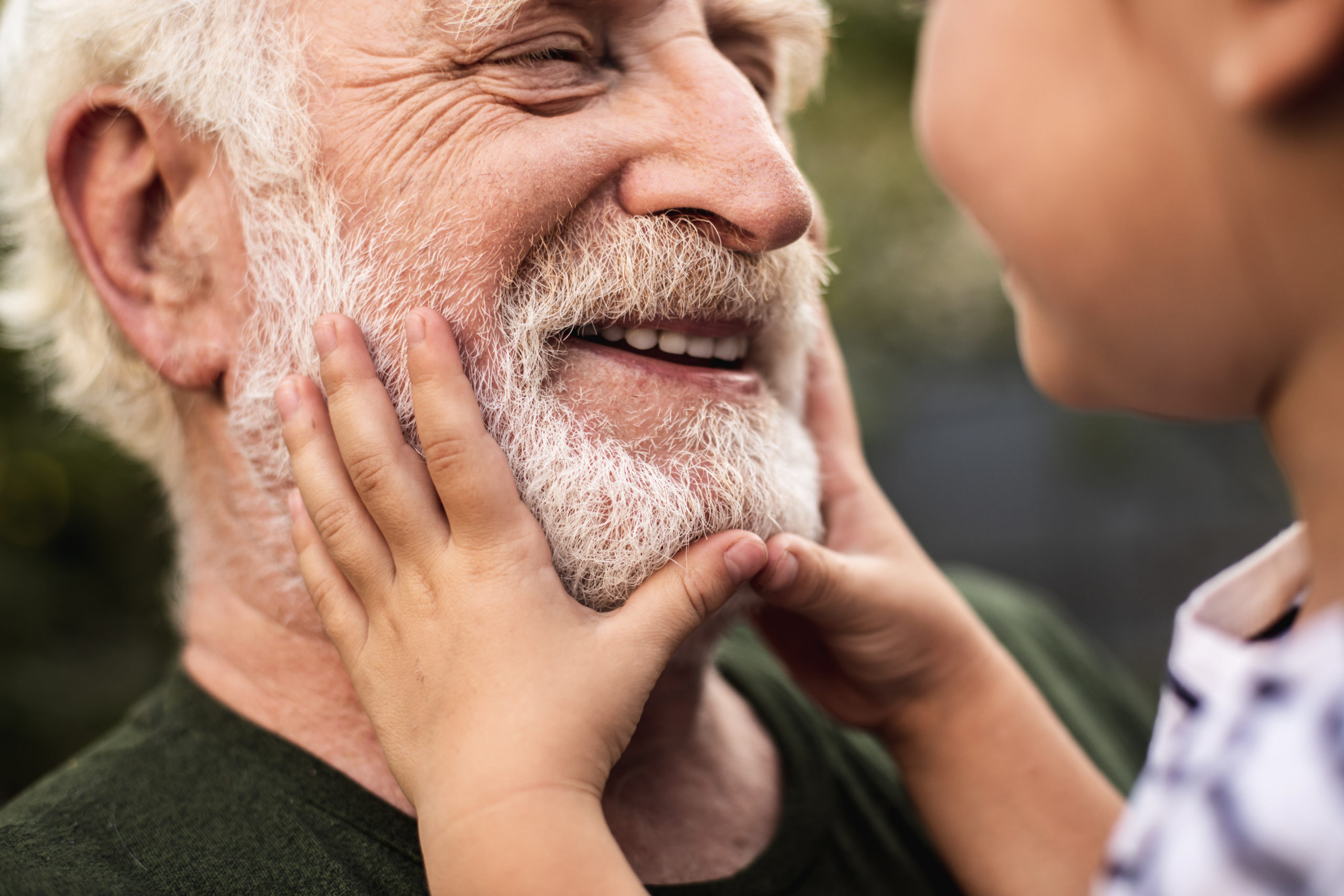 Old smiling man and his granddaughter looking each other